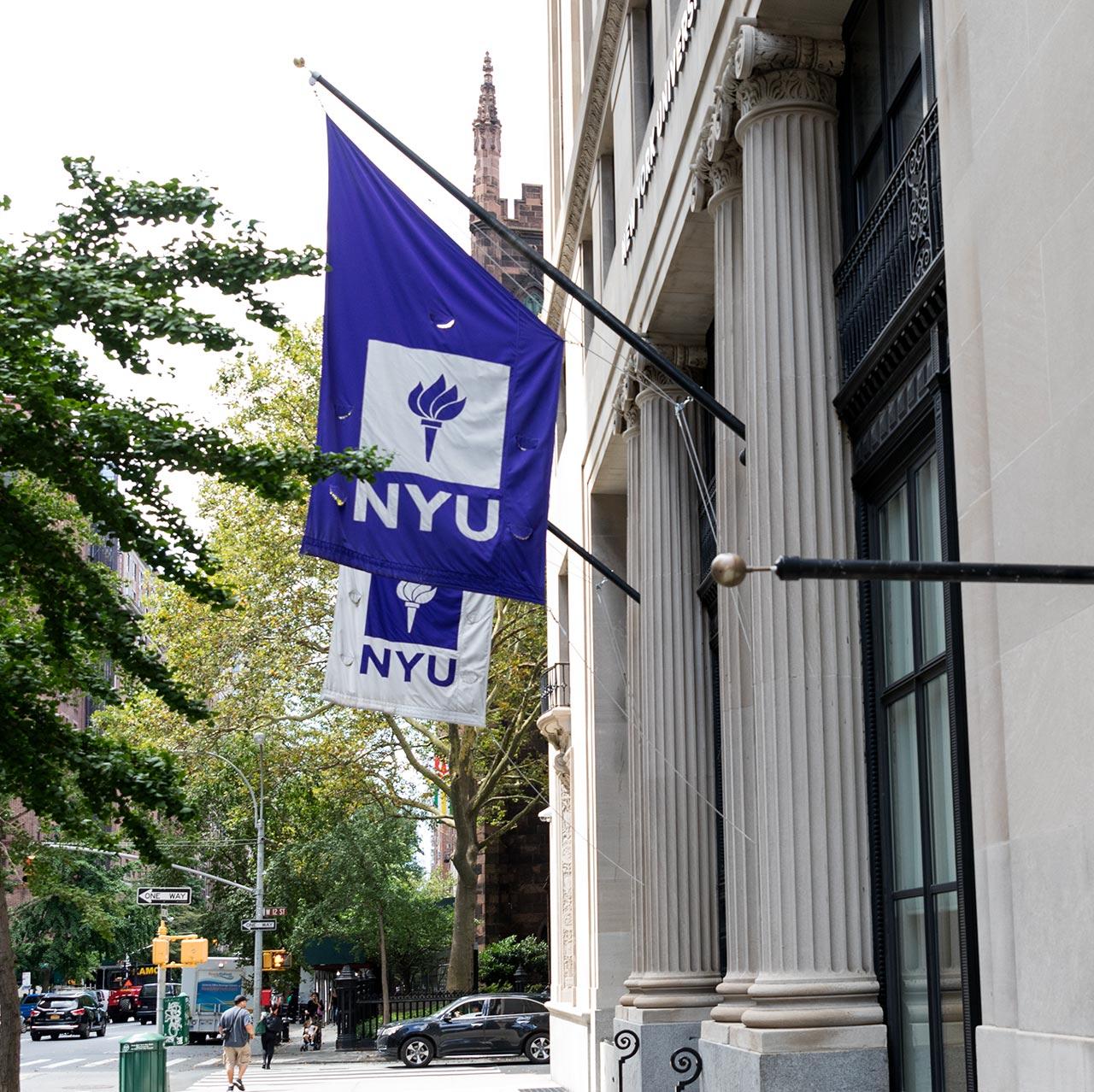 an NYU flag hangs outside of a building