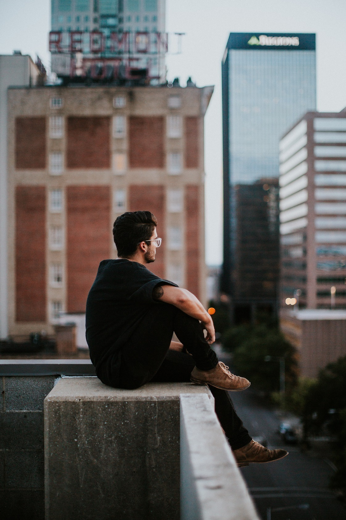 Man thinking on ledge in city.